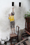 Boy Climbing Mural Painting at Penang Stock Photography