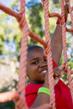 Boy climbing a net during obstacle course training Stock Photography