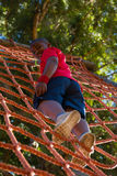 Boy climbing a net during obstacle course training Stock Images