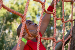 Boy climbing a net during obstacle course training Royalty Free Stock Photo