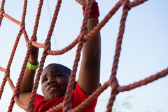 Boy climbing a net during obstacle course training Stock Image