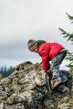 Boy climbing a peak outdoors Royalty Free Stock Photos