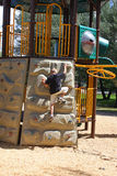 Boy Climbing On Playground. Boy climbing the rock wall playground equipment on a summer day royalty free stock images