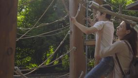 A boy climbing on a playground equipment stock video footage