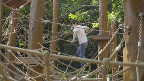 A boy climbing on a playground equipment stock footage