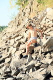 Boy climbing rock hill Royalty Free Stock Photo