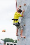 Boy climbing a rock wall Stock Images
