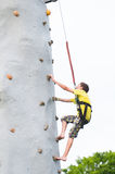 Boy climbing a rock wall Stock Image