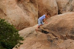 Boy Climbing On Rocks Stock Photos