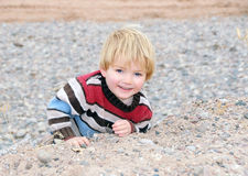 Boy climbing a rocky ledge Royalty Free Stock Photo