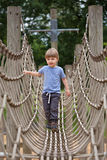 Boy climbing a rope bridge Stock Photo