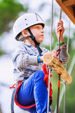 Boy climbing rope-ladder in adrenalin park Stock Photo