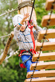 Boy climbing rope-ladder in adrenalin park Stock Image
