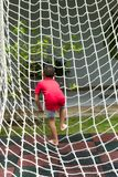 Boy climbing a rope net on the playground. royalty free stock image