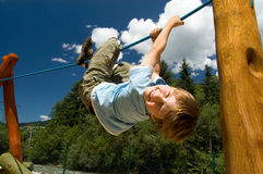 Boy on a climbing rope. Seven year old boy hanging upside down on a climbing rope on a playground Stock Images
