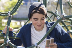 Boy climbing on ropes. A boy climbing on ropes with a mobile phone in hand Stock Photo