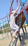 Boy climbing. A slide in a park Stock Photography