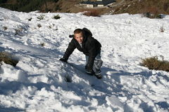 Boy climbing in the snow. A young boy playing in the snow climbing up the side of the mountain Royalty Free Stock Photos