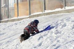 Boy climbing on a snowy hill Royalty Free Stock Photo