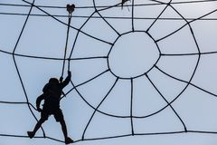 Boy Climbing Spiderweb. Young boy silhouetted in safety harness suspended climbing along spiderweb cable obstacle course Royalty Free Stock Images