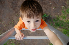 Boy climbing stairs and playing outdoors on playground, children activity. Child portrait from above. Active healthy con Stock Photography