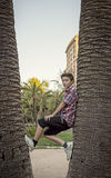 Boy climbing between tow palm tree's Royalty Free Stock Photos
