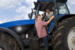 Boy climbing into tractor with grandfather Royalty Free Stock Photos