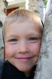 Boy climbing tree. Smiling boy climbing a birch tree Royalty Free Stock Images