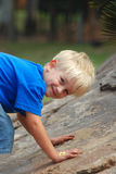 Boy climbing up. Cute little blond caucasian boy child portrait with happy smiling facial expression playing outdoors Stock Photos