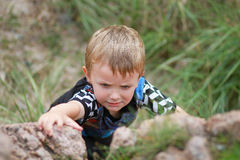 Boy Climbing up Boulder Stock Photography