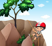 Boy climbing up the cliff Stock Images