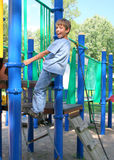 Boy climbing up ladder in a park. Boy in blue jeans climbing the ladder in a playground Stock Images