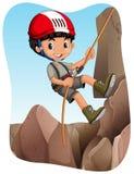 Boy climbing up the mountain Stock Image