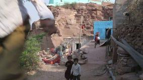 Boy climbing up the rock, with two boys standing beneath. JODHPUR, INDIA - 5 FEBRUARY 2015: Boy climbing up the rock, with two boys standing beneath stock video footage