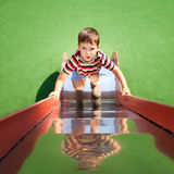 Boy climbing up a slide Stock Images