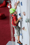 Boy on climbing wall royalty free stock images