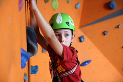 Boy on climbing wall Stock Images
