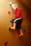 Boy climbing on  wall Stock Images