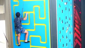Boy climbing a wall indoor. Video footage of attractive little boy climbing a wall indoor while wearing a safety rope to train his courage, strength, endurance stock video footage