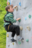Boy on climbing wall stock image