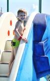 Boy climbing water slide Stock Photo