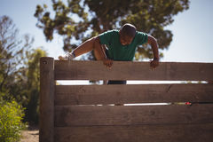 Boy climbing wooden wall during obstacle course Stock Photo