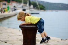 Boy climbs on bitt. Cute baby boy child with curly blond hair ponytail climbs on iron bitt bollard on sea shore Stock Photography
