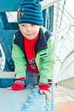 Boy climbs on the bridge Stock Images