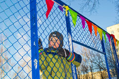 A boy climbs a fence. Boy climbing over a fence in a sunny day Stock Photo