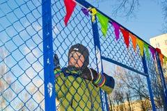 A boy climbs a fence. Boy climbing over a fence in a sunny day stock photo