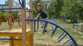 Boy climbs the metal stairs on the playground. Child climbs the metal stairs on the playground in summer stock video