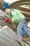 A boy climbs on a pipe Stock Images