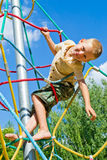 The boy climbs the ropes. On a sunny summer day at the playground Stock Image