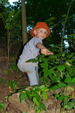 The boy climbs the slope of the ravine Stock Photo